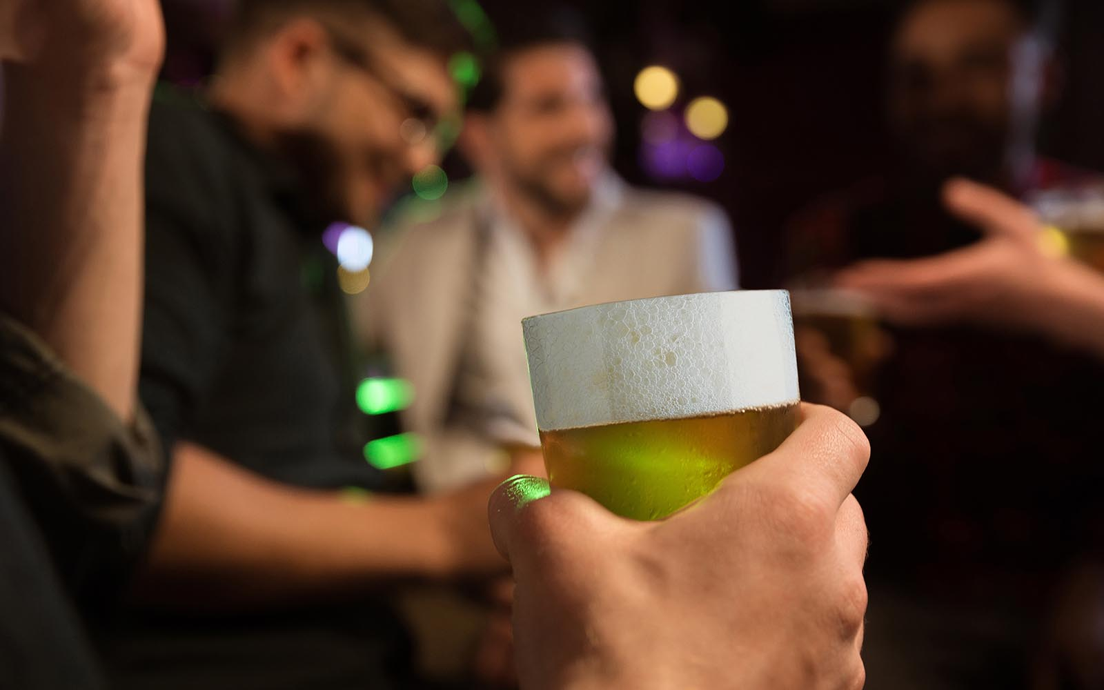 Close-up Of Man's Hand Holding Glass Of Beer While Sitting At The Bar Counter